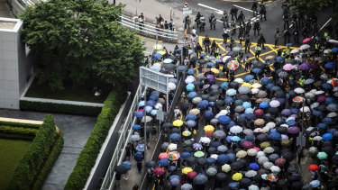 Demonstrators holding umbrellas march past riot police on Garden Road towards the Government House during a protest in the Central district of Hong Kong.