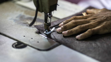 A worker uses a sewing machine while manufacturing a wallet at a leather workshop in Dharavi.