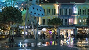People walk past nearly empty restaurants in Clarke Quay in Singapore.