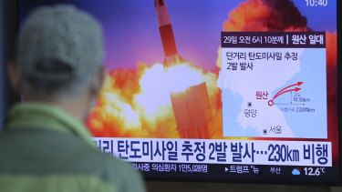 A man watches a TV screen in Seoul showing a file image of North Korea's missile launch.