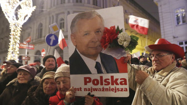 Supporters of the ruling Law and Justice party hold a portrait of the leader Jaroslaw Kaczynski as they attend a pro-government rally in front of the presidential palace, in Warsaw, Poland in 2016.