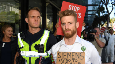 Police arrest a protester who glued his hand to a window during a protest at Siemens.