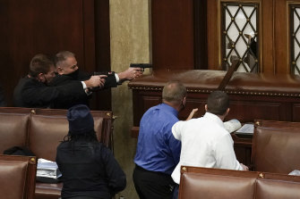 Capitol Police with guns drawn watch as protesters try to break into the House Chamber.