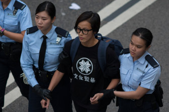 Ho, also known as singer HOCC, being escorted by police officers after a protest in 2014.
