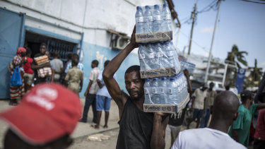 A man carries packets of bottled drinking water from a distribution centre in Beira, Mozambique, on Friday, March 29.