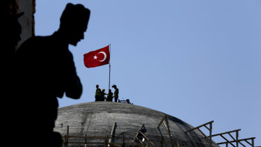 A sculpture of Turkey's founder Kemal Attaturk sits on the monument of the Republic as construction workers beyond place a Turkish national flag on the dome of the under-construction mosque in Taksim square in Istanbul.