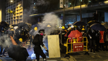 Demonstrators are shrouded in a cloud of tear gas outside the North Point Police Station in Hong Kong on Monday.