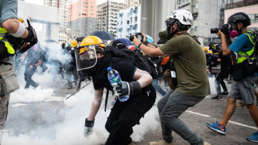 Demonstrators throw back tear gas canisters during a protest in the Yuen Long district.