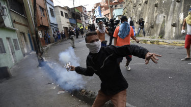 The protesters in Caracas were dispersed with tear gas as residents set fire to a barricade of trash and chanted demands that Maduro leave office.