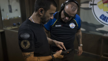 Rildo Anjos, owner of the Calibre 12 gun club, shows a pistol to club member Paulo Alberto as they stand at the shooting range in Sao Goncalo.