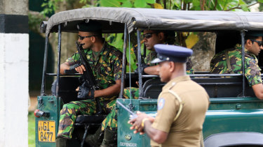 Special Task Force (STF) police officers sit in a vehicle arriving at the Parliament of Sri Lanka in Colombo.