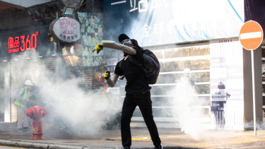 A demonstrator throws back a tear gas canister towards riot police during a protest in Hong Kong.