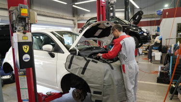 A mechanic works on a Fiat 500 at a dealership in Tokyo, Japan.