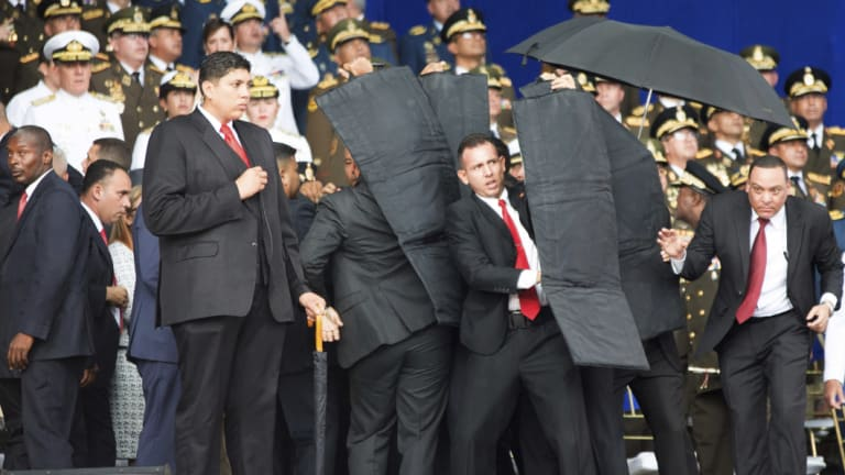 Security personnel surround Nicolas Maduro during an incident as he was giving a speech in Caracas.