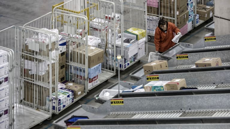 An employee handles a basket at a sorting facility inside JD.com's logistics base in Shanghai, China.