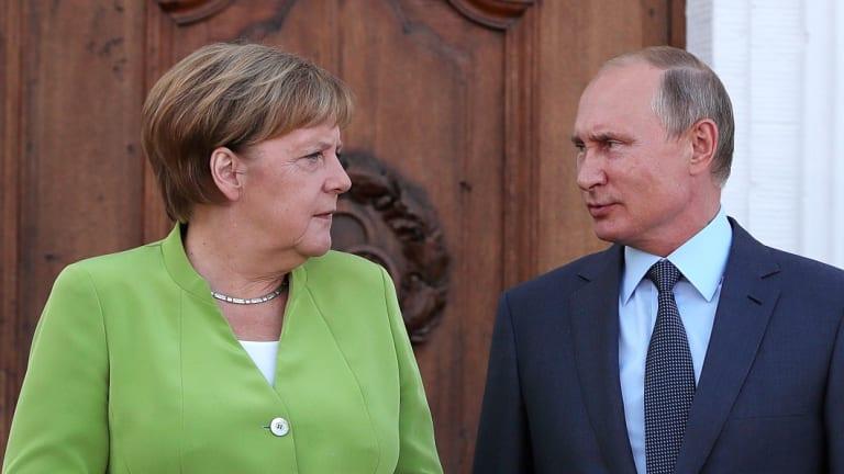 Angela Merkel, Germany's chancellor, left, speaks with Vladimir Putin, Russia's president, during a bilateral meeting at Schloss Meseberg castle in Meseburg, Germany, on August 18.