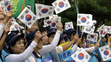 South Koreans wave their national flags during a rally to wish for the successful inter-Korean summit near the presidential Blue House in Seoul.