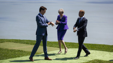 Time to unite: Justin Trudeau, Theresa May, and Donald Tusk check their watches at the G7 in La Malbaie, Quebec.