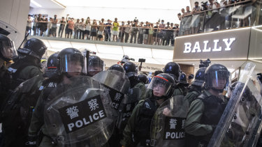 Riot police stand off against demonstrators in front of a Bally store inside New Town Plaza shopping mall.