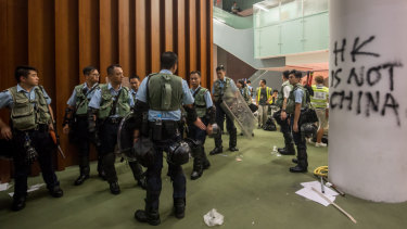 Riot police stand near graffiti inside the Legislative Council building after it was damaged by demonstrators.