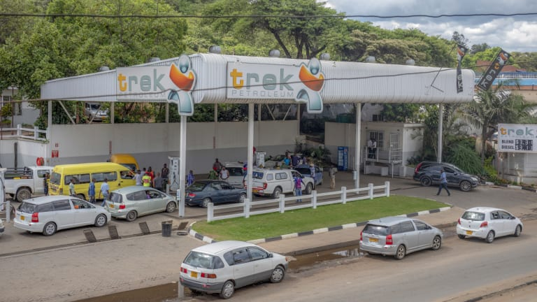 Customers queue for petrol at a gas station in Harare.
