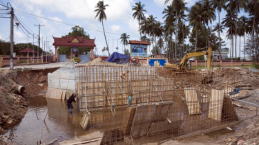 Workers labour on an under construction road outside Ream Naval Base in Sihanoukville, Cambodia.