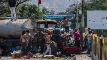 People gather near a destroyed truck on the Simon Bolivar International Bridge near the border with Venezuela in Cucuta, Colombia, on Sunday.