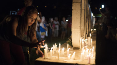 A women lights a candle at a memorial for the victims of the Brumadinho dam disaster.