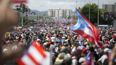Demonstrators march on a highway blocking traffic during a protest in San Juan.