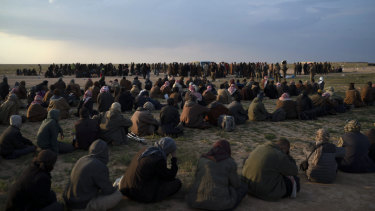 Men, foreground, women and children wait to be screened by US-backed Syrian Democratic Forces (SDF) fighters after being evacuated out of the last territory held by Islamic State militants, near Baghouz, eastern Syria, in February.