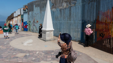 A visitor takes a photograph near a section of the US and Mexico border wall on the beach in Tijuana, Mexico.