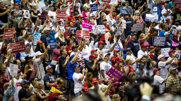 Attendees hold placards, including ones with the letter 'Q', and cheer during a rally with US President Donald Trump.