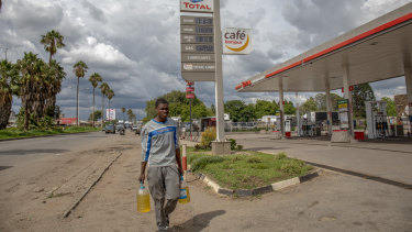 A pedestrian carries bottles containing fuel amid protests over fuel prices.