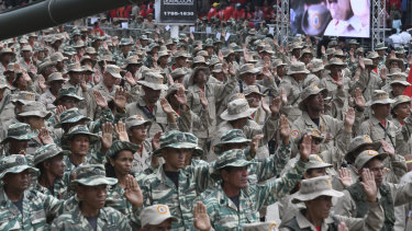 "National Bolivarian Militia members raise their hands during a military parade on ""National Bolivarian Militia Day"" at Los Proceres in Caracas, Venezuela."