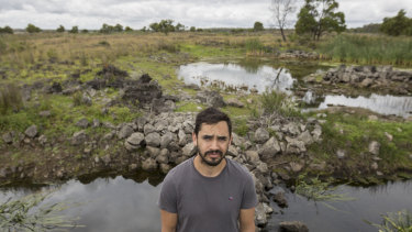 Indigenous ranger Tyson Lovett-Murray in front of a stone structure built to raise and catch eels.