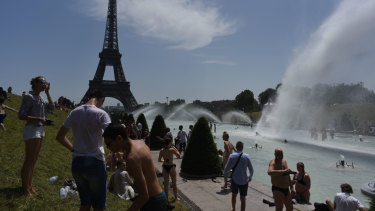 Parisians and tourists cool off in the Trocadero esplanade fountain near the Eiffel Tower in Paris on Friday.