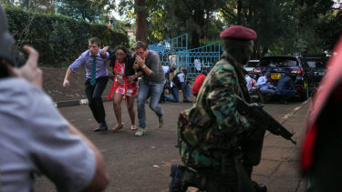 Pedestrians flee the hotel and office complex as a member of the security forces watches during an attack in the Westlands district.