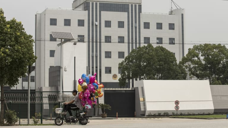 A man selling balloons ride his scooter past Qingpu Prison, where Australian citizen and former Rio Tinto executive Stern Hu was held, in Shanghai.
