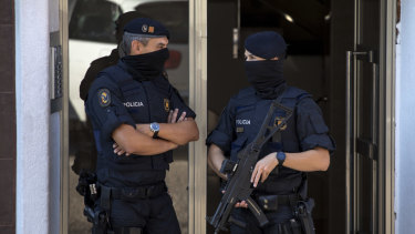 Police guard a building in Cornella after a man was shot dead at the police station.