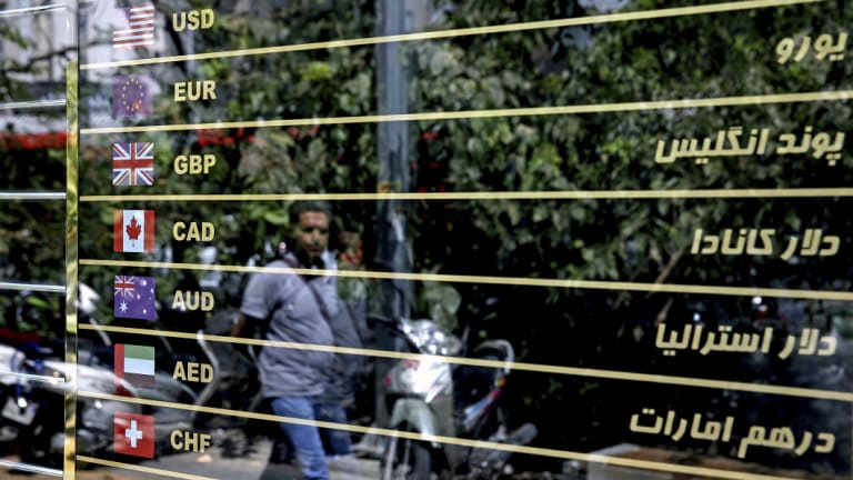 Various currencies are displayed on a money exchange bureau window in downtown Tehran.