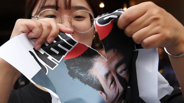 A South Korean protester in Seoul on Friday tears an image of Japanese Prime Minister Shinzo Abe. Japan announced it would restrict exports to South Korea amid a spat that puts jobs at risk jobs and threatens the global supply of microchips and smartphone displays.