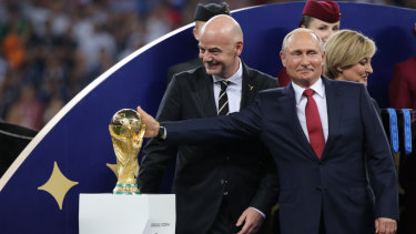 Russia's president Vladimir Putin touches the World Cup trophy as Gianni Infantino, president of FIFA, smiles during the award ceremony following the FIFA World Cup final match in Moscow, Russia, on Sunday.