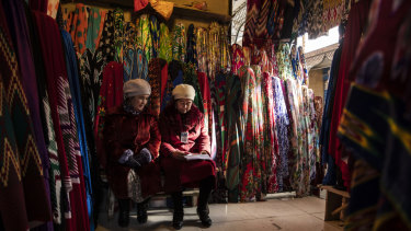 Vendors sit in a fabric stall inside the main bazaar.