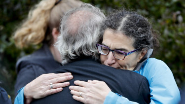 People embrace along the street in the Squirrel Hill district of Pittsburgh where a shooter opened fire during services at the Tree of Life Synagogue.
