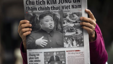 A woman reads a a newspaper featuring photographs of North Korean Leader Kim Jong-un, top, and US President Donald Trump, bottom, in Hanoi on Friday.