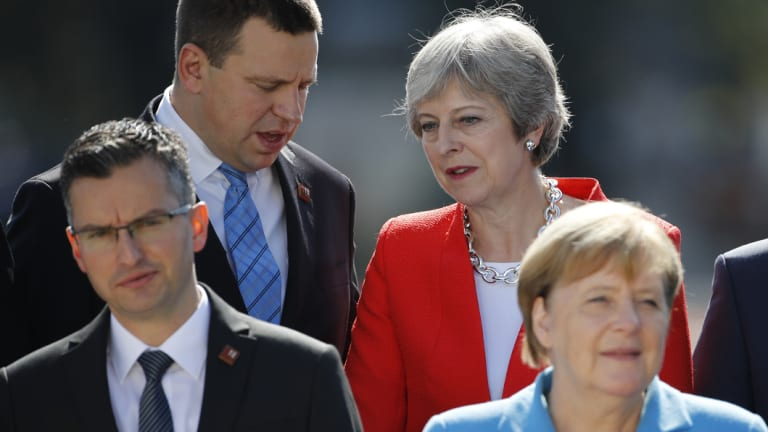 Theresa May speaks with Estonia's Prime Minister Juri Ratas during a family photo at the informal EU summit in Salzburg.