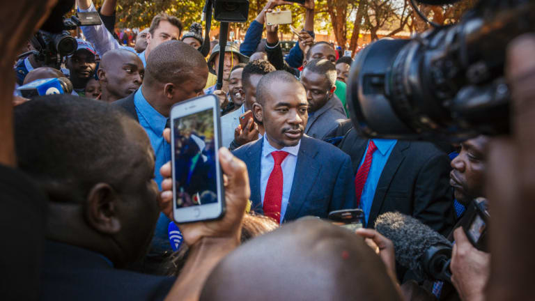 Nelson Chamisa, leader of the Movement for Democratic Change (MDC), centre, arrives to cast his vote at a polling station in the Kuwadzana township, in Harare.