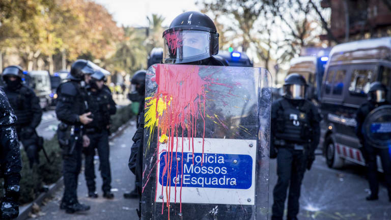 Paint splatters the riot shield and visor of a member of the Mossos d'Esquadra police force during a clash with supporters of Catalan independence on Paralelo Avenue in Barcelona, Spain.