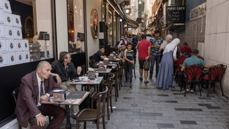 Locals sit at tables outside a tea shop on Istiklal street in Istanbul, Turkey.