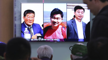 People watch a TV news report on screen displaying portraits of three Americans, from left, Kim Dong-chul, Tony Kim and Kim Hak-song, detained in North Korea.